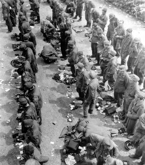 US Army MPs digging through the spread out belongings of German POWs.