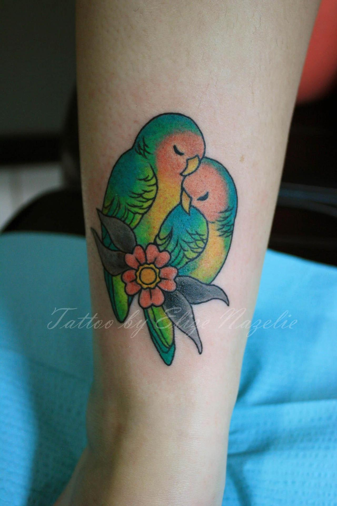 fuckyeahtattoos:  My peach-faced lovebirds <3 Done by the wonderfully talented Elize Nazelie at Empire Tattoo Studios in Somerville, MA. This was my first tattoo; I have two others being drawn up by her currently that I'm getting done in the next several months. I really love the extra detail she puts into it by adding the little eyelashes on the smaller female bird. Elize is incredibly sweet, down to earth and talented. I highly recommend her to anyone in Massachusetts or New England areas (or even further if you're willing to travel). My fiance and I have gotten each other a tattoo for each year  of our relationship. I paid for his first tattoo (for his birthday last November), he paid for this one (my first tattoo) and I'll be helping him pay for his second one, again, for his birthday. While I didn't get the Lovebirds specifically for him, I will admit that it does give me the warm fuzzies when I look at it. It'll be two years together in April; while we've had our ups and downs, I couldn't be more lucky to have found my soul mate in such a wonderful individual. He's my lovebird, so to speak <3