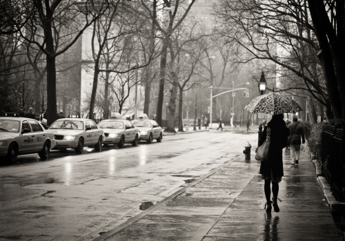 "Rain. Greenwich Village, New York City.  Rain is the sky's love song to the city.  The sky opens up revealing an other-worldly light that cloaks the city in effervescent splendor.   Sidewalks and streets, slick with promise, mirror the movement of urban explorers navigating the sleek concrete as taxi lights shine their refracted, blurred lights into the vast expanse of the rain-soaked landscape.   —-  Sharing this photo today since I talked about it (briefly) and a few other photos of mine on Trey Ratcliff's Stuck in Customs Show last night. Trey was traveling and I was asked last minute if I would be on the show with a few other street photographers to discuss some of our work. It was a great time! The other photographers on the show were Eric Kim and Rinzi Ruiz and it was hosted by Karen Hutton and Dave Veffer. I am already a huge fan of Eric's street photography but I wasn't familiar with Rinzi's work and it completely blew me away.   While the majority of my work tends to focus on New York City's landscapes and architecture and is devoid of people, it was nice to discuss a few of my photos that do have people in them and talk a little bit about my philosophy on shooting people in the city and the narratives I tend to gravitate towards when dealing with people shots.   It's always interesting to see how certain themes emerge with any art form and I seem to have a fondness for street photography in the rain. I blame New York City for that fondness. It's just so incredibly moody and beautiful when it rains here :).   You can view the show from last night here: Trey's Variety Hour #53: Street Photography  —-  View this photo larger and on black on my Google Plus page  —-  Buy ""Rain - Greenwich Village - New York City"" Prints here, email me, or ask for help."
