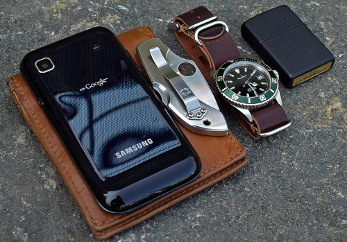 submitted by Sergiu M  This is what I have in my pockets today: *Samsung Galaxy GT-I9000*Fossil tan bi-fold wallet*Spyderco Dragonfly VG10*Marcello C Nettuno 3 watch on a Shell Cordovan nr. 8 leather NATO strap*Zippo lighter I recently repaired my Olympus DSLR and even though I have yet to learn how to use it properly, I hope this picture is a bit closer to the high standard of the great submissions on your blog.  Editor's Note: Nice carry here — albeit even more minimal than most (no keyring?). The Dfly is a nice little EDC knife, I love the blade shape on it. I don't see leather NATO straps very often, but the pairing of the cordovan and that dark green bezel is awesome! That finish on your Zippo looks great too. I'll assume your smartphone has an LED flashlight in it, otherwise a light could help round out the rest of your carry. Thanks for sharing!