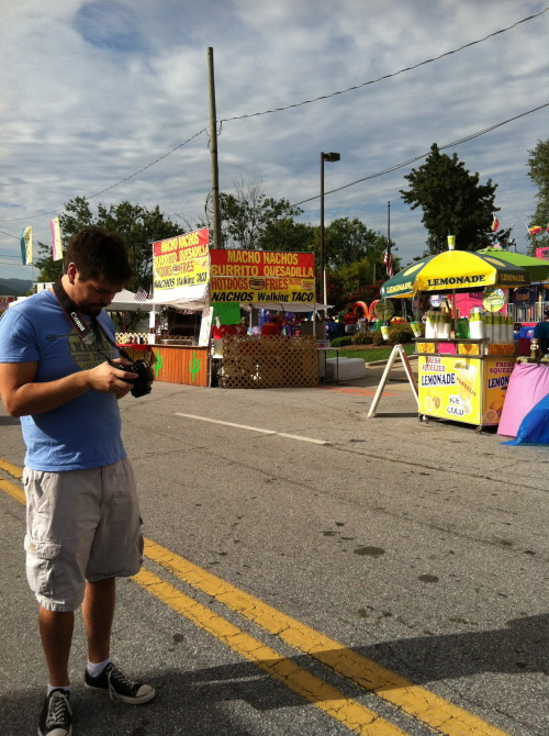 "A few weekends ago we went to the Hendersonville Apple Festival, the largest apple festival in the state of North Carolina. The mountains rose blue and smooth in the distance, and I would later find a sunburn on my chest, creating two thin strips of pale skin under the lines of my tank top. Various community organizations collected five dollars' parking fare in the blocks around the festival. We gave our money to Hendersonville Junior Basketball League, at the far end, where all the festival food was.              We went into the general store that Ben had loved when he was a little kid and browsed antique store displays from the sidewalk. I bought a chocolate cream-filled doughnut for eighty-five cents, and it was the best doughnut I had ever had. Ben had his camera out, snapping pictures in the perfect light, while I walked and exclaimed at every booth. I tried every apple product I could bear. Apple butter, fried apple pie, the most delicious pretzel with apple cinnamon bits embedded amidst the salt, and a quarter peck of fresh apples to take back to the tiny mountain cabin where we were staying.              Ben got a caramel apple as his only apple product of the day, a restraint that neither I nor my stomach could fathom. He'd walked past two caramel apple salesmen before he settled on one he felt looked right and cost an acceptable amount, three dollars.              ""You know,"" he said thoughtfully as we ambled, ""I've never actually had a caramel apple.""              ""What?"" I laughed. ""Why were you so insistent, then?""              ""Dunno,"" he said, gnawing at the caramel. ""Just seemed right. Apple festival, I feel like you should get a caramel apple.""              We walked like that in the mountain sunlight and it was a brilliant, beautiful day."