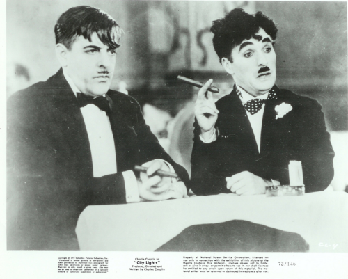 "Criterion Caravan #7: City Lights (1931) by Charlie Chaplin.  Continuing my chronological journey through the Criterion Collection as available on VOD. When we last visited with Mr. Chaplin at the start of this journey, I discussed my preference for Buster Keaton over Chaplin and my outrage that Chaplin's star has eclipsed his with film nabobs.  Returning to him for City Lights, perhaps his most loved (if not studied) film did nothing to change my mind.I'm sorry. I recognize he is brilliant with the physical comedy, and that his later films he did the world some kind of great service by littering them with hamfisted dollops of schoolboy Marxism.  But I just find him overly mannered, prim, prissy and too absorbed in the antics of his own movements.  Unlike Keaton, whose physical comedy is soaked in pathos, Chaplin is ""clever"" and amusing, but emotionally barren.I will say this however: for a bit it seemed like City Lights was leading up to the most horrifying tragic denouement history would have seen.   While it seemed it was going that way I was in awe and delight.   Spoiler recap:  The tramp saved a drunk rich man from killing himself.  When they went back to the millionaire's house, he said - still drunk - how can I thank you.  The Tramp asked for money so the blind girl he was in love with could get an operation to not be blind any more.  The millionaire handed it over.  But then there was a break in and the police came.  The millionaire sobered up and didn't remember giving the tramp money.  The tramp fled to the blind girl and handed the money over to her to get her operation and then turned himself in.  Months later, the tramp is released from prison, a shell of the tramp he once was.  Such a mess that boys kick him in the street.  He passes a shop window and sees the blind girl at work.  Only now she can see.  But she sees him and mocks the desheveled wreck of a tramp in the street.  Oh the irony.  And if it had ended there it would have been the most wonderfully cruel ending since Esmerelda rode off and left Quasimodo talking to the stones, since Angela got in the car with Jordan and left Brian Crakow standing in the street.  If it had ended just one shot earlier City Lights would have joined those ranks.  But it didn't and instead gave us a very last second happy ending, which as much as one would like to pretend the film did end a half second earlier, you just can't unsee.  And so the film ends up another whimsical Chaplin titterer.  Which if that's your thing, you will love.  I'm sticking with Keaton and from here on I will exercise the Caravan driver's prerogative to not skip over the rest of a director's entries after I have seen two of his films.  I know they are all important and historic.  But we're still only 1931 and have miles to go before we sleep. Next up: Another visit with Rene Clair for his ""lyrical masterpiece"" Le Million."