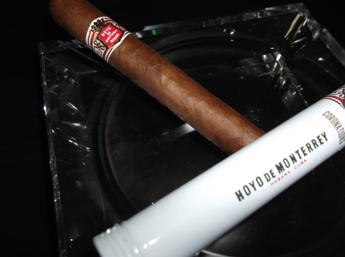 """Hoyo De Monterrey, Coronation"" (5 1/8x42) (Cuban) CC Rating: 89 This rugged looking cigar featured a reddish brown wrapper with small veins and no tooth present at all. The pre lit aroma consisted of faint wood and tobacco notes. The ash was a light grey color with a fairly even burn for the entire cigar. The draw was slightly on the loose side, producing tons of flavorful medium bodied smoke. The first third provided flavors of strong leather and coffee notes with a faint sweet cream flavor on the draw. The finish consisted of a big blast of pepper which mixed with wood notes. Reaching the second third, the cream had lost most of its sweetness from the first third. The draw flavors mainly consisted of the same leather and strong coffee notes with the coffee continuing into the finish mixing with pepper and faint wood notes. The final third continued with the same flavors which were previously mentioned. The draw consisted of a creamy coffee with hints of pepper and black coffee notes on the finish. The pepper had died down, losing its intense heat. The flavor profile was left with the pepper flavors mixing with the overall profile. This cigar would go perfect with a strong cup of coffee in the morning to have with your breakfast! Stay Toasting!"