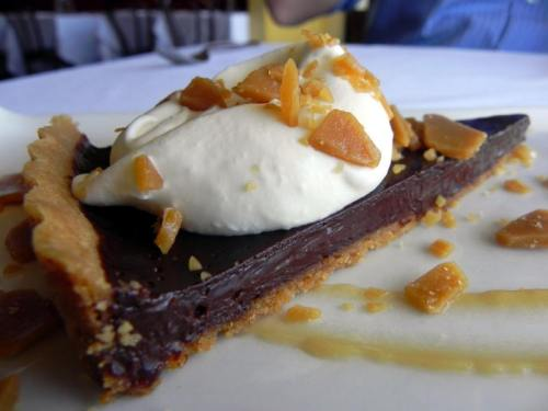 Toffee Chocolate Tart with a shortbread crust topped by coconut whipped cream and toffee bits from La Petite Grocery