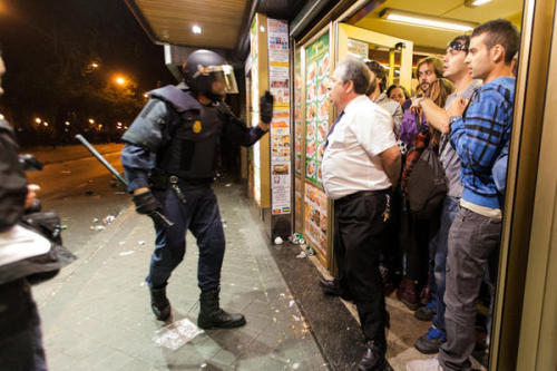 "Photo of the Day: Bar owner defending protestors against the police. Spanish Redditor NonPlusUltraCadiz describes the photo:   Police were trying to enter his bar (""Get in and proceed to detentions"" are the textual words), while protestors threw stones and bottles at the Police. Inside, more protestors try to hide from the Police. The owner denies entrance to the Police (""No Police is going to enter here because everyone here is an innocent citizen"") [The police] try to lift him from the door. He stands, near to tears, and shouts to the people throwing things: ""STOP THROWING STONES, PLEASE"". He was defending the protestors, but also defending his bar from the stones!  via"