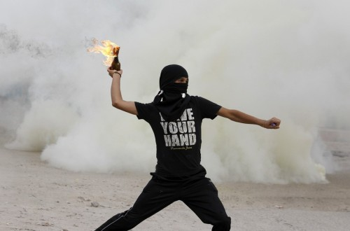 An anti-government protester throws a molotov cocktail at riot-police during clashes at the mourning procession of the murdered Ahmed Ismael Abdulsamad in the village of Salmabad south of Manama, April 2, 2012. Abdulsamad died early Friday from a single gunshot wound to the thigh fired from a moving car, a Ministry of Interior statement said. REUTERS/Hamad I Mohammed  more amazing pics of the anti-government protest in Bahrain here.