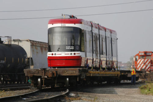 "(via TTC's new streetcar spotted in the Junction - thestar.com)  The first test vehicle of the Toronto Transit Commission's new streetcar fleet has arrived in the city, sending ripples of excitement through Toronto's transit-hungry trainspotting community. Bombardier shipped the new streetcar to the Canadian Pacific rail yard near Runnymede Rd. and Dundas St. on Tuesday, where it will stand until it's lifted onto a flatbed and trucked overnight to the TTC's Hillcrest yard at Bathurst St. and Davenport Rd. TTC officials aren't saying when that will happen. Not surprisingly, reports and photos of sightings hit the internet almost immediately. ""We are a streetcar city and at the TTC we're very excited to be receiving this test vehicle and we're looking forward to get the vehicles out in service,"" said TTC spokesman Brad Ross. The vehicle, still officially owned by Bombardier, is the first of three test vehicles. Unlike previous prototypes that have been shown off in Toronto, this one is a working model and will be put through its paces, first at the TTC's Hillcrest facility near Davenport Rd. and Bathurst St., then next year, across the entire streetcar network. It will be 2014 before the first cars of the new fleet go into revenue service."