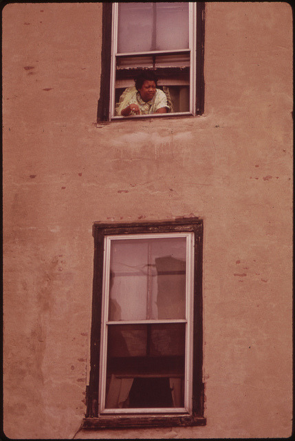 Woman looks out her Window.