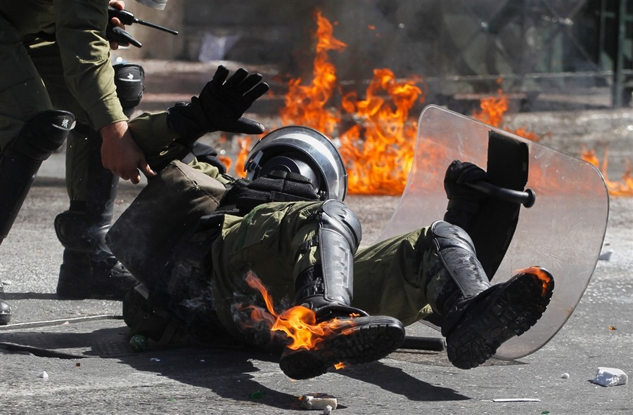 politics-war:  A riot policeman reacts after he was hit by a petrol bomb thrown by protesters during a nationwide general strike in Athens on Sept. 26.    via TumbleBoard for iPad