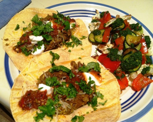 Lentil Tacos with Chimichurri Vegetables  Original taco recipe from Budget Bytes Original vegetable recipe from Meatless Monday  I'd been eyeing this taco recipe from Budget Bytes for a while, and yesterday seemed like the perfect Taco Tuesday to try it out. Beth's recipe has you make your own taco seasoning, but I was lazy and just used a package. The lentils are tasty and a good alternative to your standard meat/fake meat taco filling options. This was our second time having the chimichurri vegetables. They're an easy side dish that would work well with many types of meals. Chimichurri is definitely greater than the sum of its parts. I mean parsley is alright, but it's certainly no cilantro or basil. Warning: it's spicy, so cut down on the chili flakes if you have milder tastes. Ingredients  For the tacos: 2 cups brown lentils 1 small onion, diced 2 garlic cloves, minced 2 tablespoons olive oil 1 packet taco seasoning or use this recipe 1 teaspoon salt 12 corn tortillas Salsa Sour cream Shredded Mexican blend cheese Hot sauce Cilantro, chopped For the vegetables: 1 bunch parsley, stems removed 1 clove garlic 2 teaspoons red wine vinegar 1 teaspoon red pepper flakes 1/2 teaspoon black pepper 1/3 cup plus 2 tablespoons olive oil, divided 1 head cauliflower, broken into small florets 1 medium zucchini, sliced 1 red bell pepper, sliced Directions  For the tacos: Sort and rinse the lentils. Bring 3 cups of water to a boil in a pot. Add the lentils and let the pot return to a boil. Reduce the heat to low, place a lid on top. Allow the lentils to simmer for 20 minutes. Taste the lentils to test the texture. They should be tender but not mushy. Drain the lentils in a colander.Heat the olive oil in a large skillet over medium heat and cook the onions and garlic until tender. Add the drained lentils, the taco seasoning, and about a half cup of water. Stir and cook over medium heat for 5 minutes. Season to taste with salt.Heat the tortillas. Build the tacos using about 1/3 cup of seasoned lentils per taco and whatever toppings you like.  For the vegetables: Preheat the oven to 400 degrees.  Place the parsley, garlic, red wine vinegar, red pepper flakes, black pepper and olive oil into a blender or food processor. Blend until thoroughly combined. Transfer to a bowl and set aside.  Toss the cauliflower florets on a baking sheet with a tablespoon of olive oil. Roast the cauliflower in the oven for 30 – 40 minutes, or until the florets begin to turn golden brown.  15 minutes before the cauliflower florets have completed roasting, heat the remaining tablespoon of olive oil in a skillet over medium. Place the sliced zucchini and bell peppers into the skillet and cook, stirring occasionally, for 10 - 15 minutes, or until the bell peppers become sweet, soft and fragrant.  Divide the cauliflower and sautéed zucchini and peppers into 4 portions. Drizzle with chimichurri sauce.  Servings: 4  ♫ Music Pairing: R. Kelly – In the Kitchen  Getting super pumped to finally see Kells live in concert on Halloween!  This is what it's going to be like
