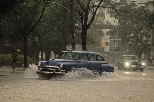 Cars driving through flooded streets during a tropical thunder storm in Havana, Cuba