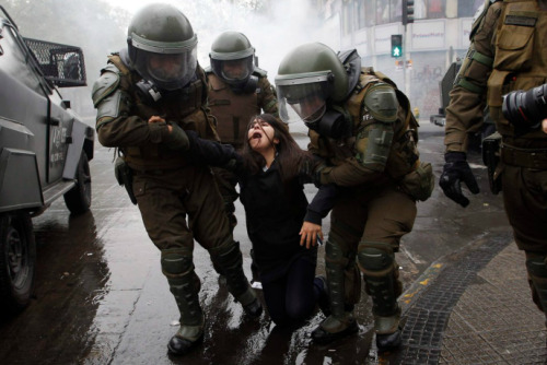 simply-war:  A woman in Santiago, Chile, was arrested during student demonstrations to demand improvements to the national education system. Photography by; Ivan Alvarado