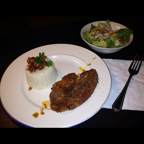 Grilled Blackened Tilapia, rice pilaf w/ candied bacon, caramelized spring onions & fresh parsley with a side Caesar salad! (Taken with Instagram)