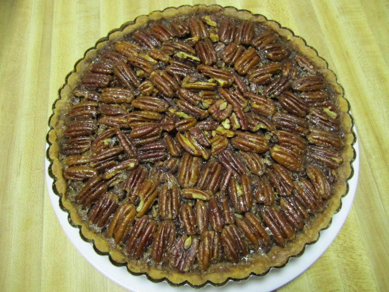 "foodisforeating:   Chocolate Pecan Pie: chopped pecans, brown sugar filling cut with some Kahlua, chopped chocolate, pâte sucrée crust.  Shown with a scoop of vanilla ice cream from Halo Farm (Trenton, NJ)  Traditionally, pecan pies contain corn syrup in the filling to give the dessert its signature chewy mouthfeel.  What corn syrup also imparts, though, is that cloying sweetness that many like myself just can't get behind.  This particular pie, however, differentiates itself from these other pies in that it not only uses brown sugar instead of corn syrup but also that it cuts the sweetness further with some chocolate and a little liquor (I used Kahlua since there was no cognac on hand).  The results were good, even though I made some errors which affected the final result. That means that I'll have to be doing some more pecan pie ""research,"" but I'm sure I can easily find some guinea pigs to test my food…"