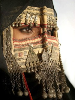 "folkthings:  Rashida woman, Eritrea""The Rashida are descendants of 19th-century immigrants from Saudi Arabia presently occupying the area centered around Kassala in Sudan, though occasionally traveling through the Eastern Desert to Shalateen. They usher large herds of camel from Sudan through the inhospitable terrain to sell them at Shalateen's camel market, where traders from all over Egypt bargain for camel deals. They are an interesting people, and don't really comply with the rules of a normal citizenship; relocating from place to place and trading in absolutely everything; buying and selling locally made handicrafts such as jewelry, knives, and swords.As in other Arab tribal traditions, the women consider their mouth to be one of their private parts, and always have it covered, as well as most of their body, even in 40+ degree heat. They wear colorful fabrics and craft many things out of beads such as wall hangings, veils and jewels. Women of the Rashida tribe make the silver jewelry. In wedding celebrations men show off their warrior skills, staging sword fights. Tribesmen cheer around the two dueling swordsmen, waiting for their turn. The swordsmen dual fearlessly, clashing their swords in blazing speed while kicking dirt at their opponent's face. In another part of the camp sheep and goats are slaughtered for the feast.They love to have their picture taken and often crowd around for a photo.""—> SOURCE OF THE TEXT <—"