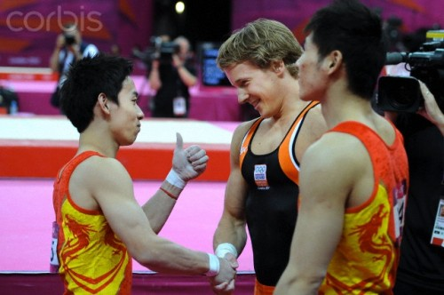 China's bronze medalist Zou Kai and gold medalist Epke Zonderland of the Netherlands (L-R) celebrate their medals in the men's horizontal bar event during the 2012 London Summer Olympic Games. (Photo ITAR-TASS/ Valery Sharifulin)