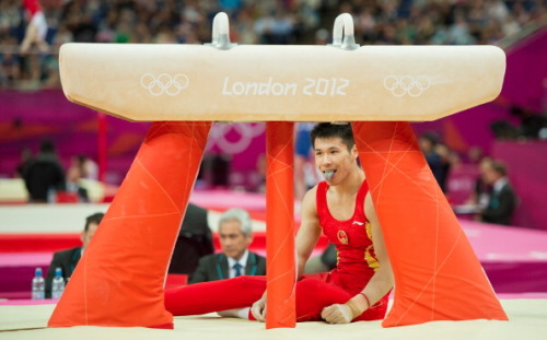 China's Chenglong Zhang reacted after falling off the pommel horse in men's team gymnastics preliminaries competition at North Greenwich Arena during the 2012 Summer Olympic Games in London, England, Saturday, July 28, 2012. (Photo Credit: David Eulitt/Kansas City Star/MCT via Getty Images)