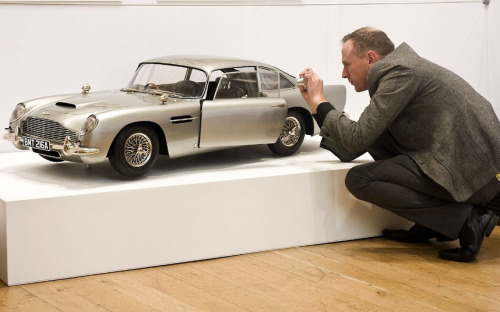 thepastichom: 50 Years of James Bond, the auction at Christie's in London A man photographs a post-production one-third scale replica miniature model of the Aston Martin DB5 used in the film Skyfall. Estimated sale value £30,000-40,000. Picture: Ray Tang / Rex Featureshttp://telegraph.co.uk