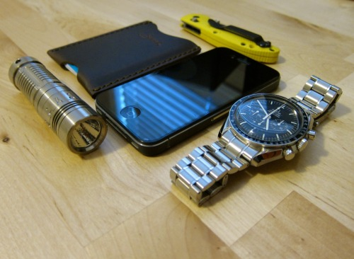 "submitted by Tim  Love the site. I check it out daily. Here is my EDC:Sunwayman V10R Ti Flashlight - This is a great little light. It has variable brightness from 1-210 lumen. I also have the AA extender so it can use AA or CR123A. It is tough, light and looks great. Saddleback Leather Wallet Sleeve - I am always on the lookout for a slim wallet and have gone through quite a few and this is my favorite so far. The leather quality is fantastic, and I only carry 4 cards with me so it is barley noticeable in my pocket.iPhone 4 - Can't live without this, connects me to the world.Benchmade Doug Ritter Mini-RSK Mk1 Knife -  Basically a mini Griptilian with S30V steel and a great handle. Stands up to anything I throw at it and looks good doing it.Omega Speed Master Professional Watch - I've been through a few watches but I think I have finally found my ""one"". I love the tough hand wound movement, great looks, classic lines and feel on the wrist. It's designed to go to space so I am sure it can handle anything I can throw at it.  Editor's Note: Hi Tim, thanks for your support. I just want to say you have an excellent EDC, and I appreciate your taste in both aesthetics, practicality and quality. The V10R looks to have a great user interface, the battery versatility as you mentioned, and it sure is a looker. The Saddleback is renowned for its durability and opting for a slimmer type of wallet is better to carry, especially if you keep it in your back pocket. Good choice on the Ritter minigrip as you get a premium steel on a great EDC knife (its blade shape, length, lock, handle and clip). The scale color is perhaps not as low key but at least it's got a friendlier, colorful appearance that should also help with visibility if you need to grab it quickly. Lastly, gorgeous watch… Wear it well and in good health! Thanks for sharing."