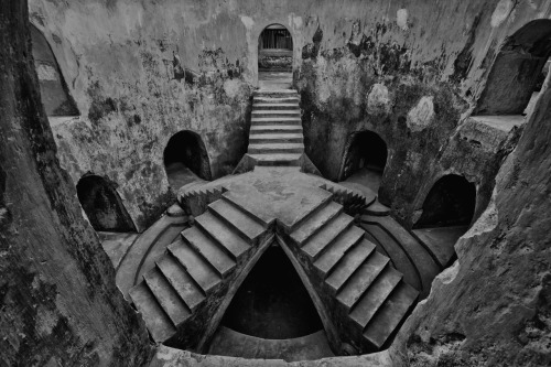 "fuckyeahphotographics:  The Underground Mosque, known as Sumur Gumuling"", in Yogyakarta, Indonesia was built upon a circular well in 1750. The building is totally underground, surrounding the well (sumur). Four stairways above the well meets at the center, forming a small stage and a fifth staircase leads to the upper second floor. These stairways symbolizes the Five Islamic Principles, the highest staircase referring to the pilgrimage to Mecca for Muslims. The Imam would stand on the small stage formed by the set of stairways, taking advantage of the excellent acoustics of the circular building to deliver his sermon. The mosque is part of the greater complex of Taman Sari, where underground tunnels link to the Royal Palace, the Water Castle, a pleasure bath complex for the Sultan, his family and concubines and to the South Java Sea. Many of the tunnels are closed for safety reasons. Much restoration work need to be done in this Complex before it can be officially be listed as an UNESCO Heritage Site.  I have been there and this place is REALLY great and cool."