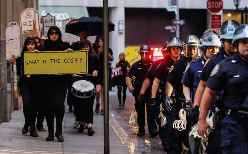 Occupy Wall Street activists are watched by New York Police Department officers while demonstrating in the financial district during an action held to mark the first anniversary of the movement in New York (via Occupy Wall Street protesters hold rally in New York to mark anniversary - Telegraph)