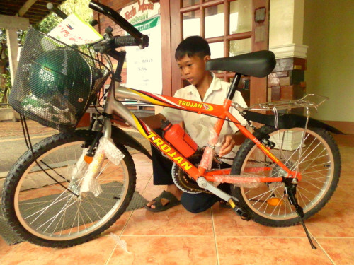 "JHONLEE'S NEW BICYCLE: The Korea Environment Corp. partnered with ChildFund Korea to provide bicycles to children in the Philippines who must travel long distances from their homes to school. Each child received a brand-new bicycle, a riding helmet, a small air pump and a tire repair kit. ""I'm going to install a wooden board here,"" says Jhonlee, pointing to the section of frame between the seat and handlebar. ""That way, my two [younger] brothers can ride while I pedal us to school,"" he explains."