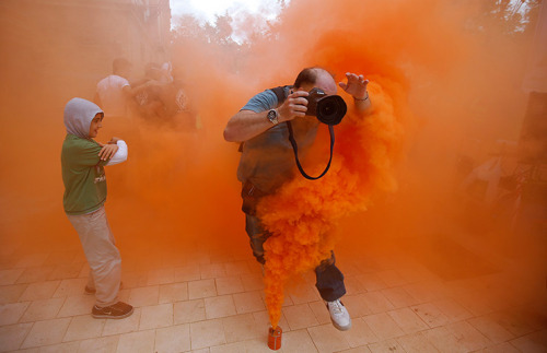 inothernews:  AGENT / ORANGE  A photographer jumps over a smoke canister during a protest by firefighters, security and military personnel in Seville, Spain against cuts in their salaries imposed by Spanish government. (Photo: Marcelo del Pozo / Reuters via The Guardian)