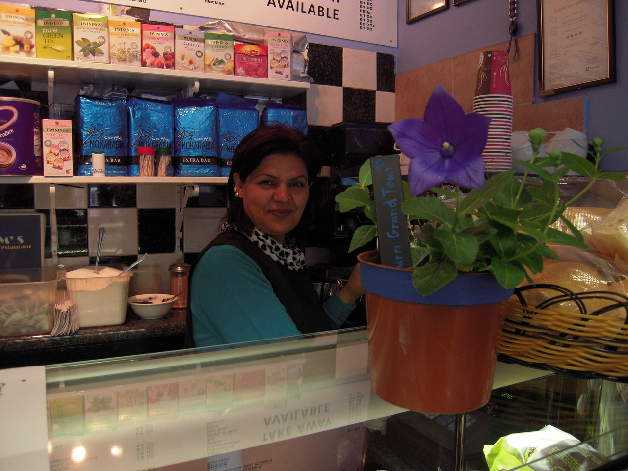 The second Blue Flower cooperator!  Tim's Cafe 5 Quex Road,London, NW6 4PP  In the photo:  Fawzia  Manager's name is Rosey  Rosey said :  I love Kilburn. I've lived here since 1996 and had the business for ten years now. I know the local people and they are all really good people, at first it can be hard to know them but once you start to chat you see they are all such good people. It's a good community here. On Monday through to Friday I have my local regulars come in, on Saturdays I get people from all over London who come for the shopping on Kilburn High Rd and on Sundays people come after Mass from the two local churches.