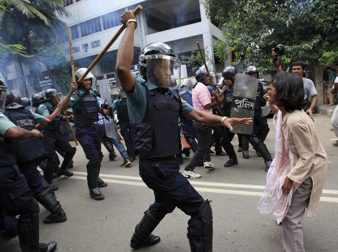 A police officer uses his baton to hit an activist from the National Committee to protect Oil, Gas, Mineral Resources, Power and Ports during a protest against the government in Dhaka September 30, 2012.  Demonstrators demanding the government withdraw the recent power tariff hike marched towards the city's energy ministry on Sunday, but were dispersed by local authorities using batons and tear gas, according to local media. [REUTERS/Andrew Biraj] PHOTOS: Reuters images from the past 24 hours