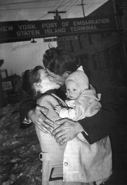 allaboutthepast:  A soldier is welcomed home by his wife and baby, 1940s.