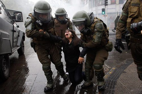 politics-war:  Riot police arrest a student during protests against government changes to the state education system in Santiago, Chile. Photograph: Ivan Alvarado