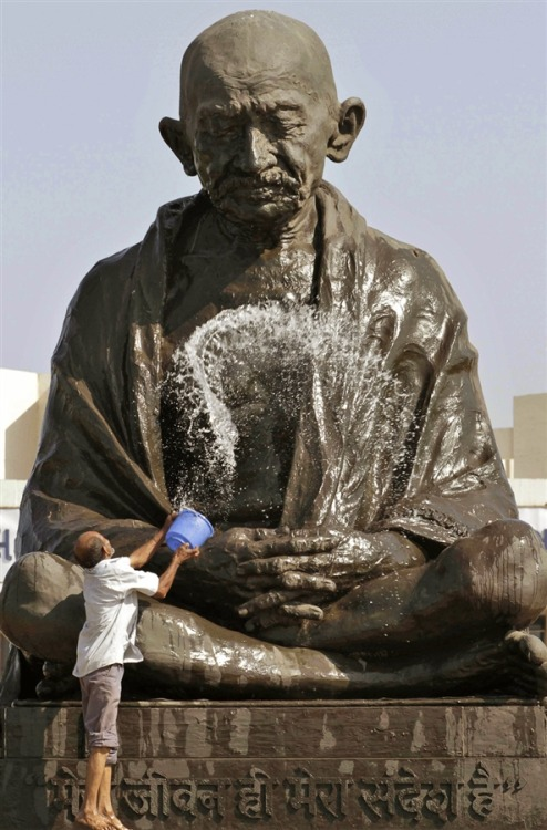 aa-hafiz:  politics-war:  A man throws water on a statue of Mahatma Gandhi as he cleans it on the eve of Gandhi's birthday at the Gujarat state legislature complex in Gandhinagar, India, on Oct. 1, 2012. Gandhi was born on Oct. 2, 1869.  موعد الاستحمام السنوي لغاندي