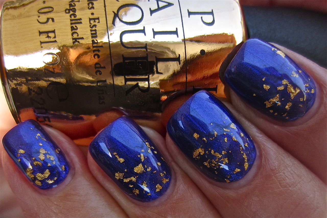 "The ""Man with the Golden Gun"" topcoat from OPI's Skyfall James Bond Collection. With real 18K gold! Swatched over ""Tomorrow Never Dies"". Beautiful, isn't it? Photo from Ommophoria Beauty Bar."