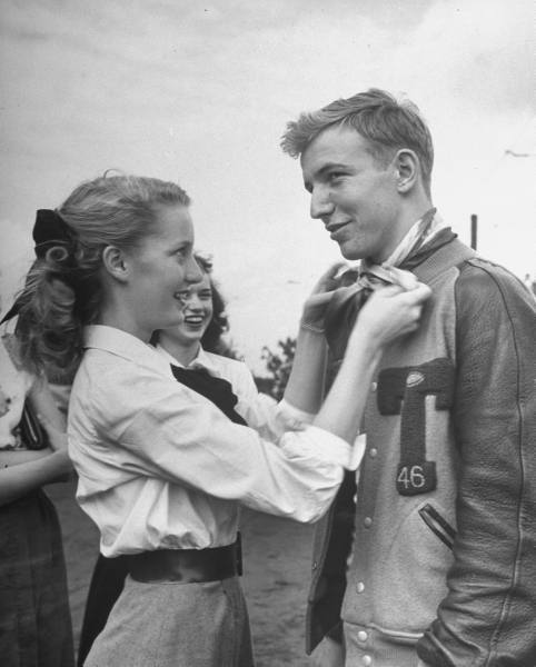 1950sunlimited:  Teen Fads, 1947    Girl ties her hair scarf around her boyfriends neck as a fond token. Boy often gives football sweater as token to his girl.