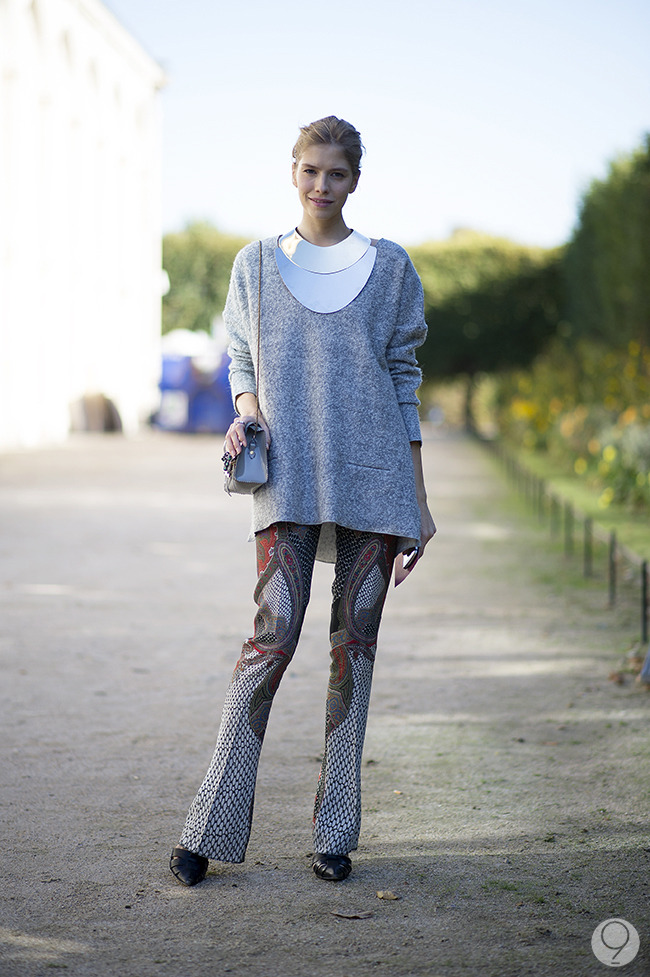 Street Style: Elena Perminova creates a chic, modern look for Paris Fashion Week by playing up a gray sweater with paisley pants and an armor-like statement necklace. Via I'm Koo.