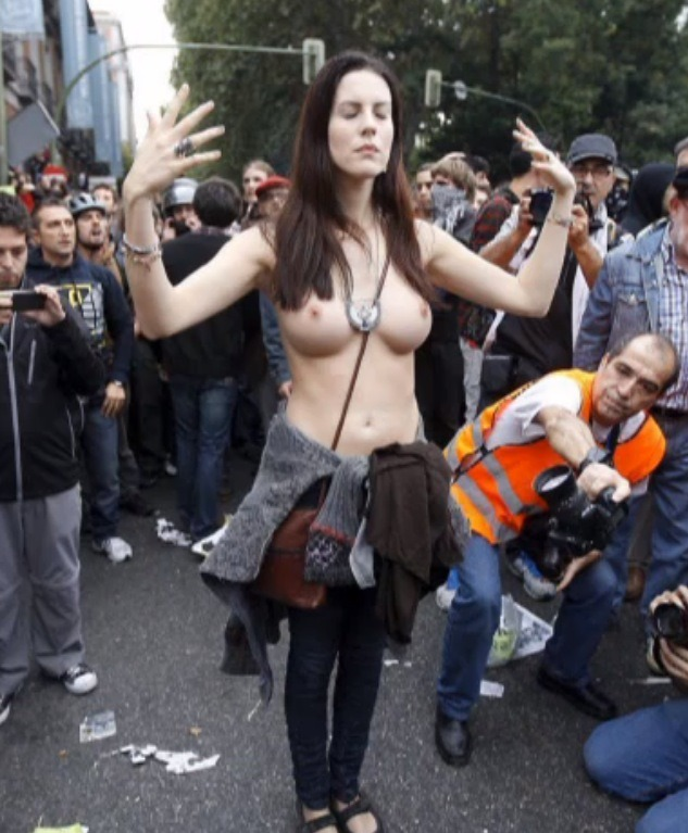These Boobs Kill Capitalists What with the overthrowing of the Spanish government not really happening and skulls getting cracked left, right, and center, the 25-S protests in Madrid last week turned out to be a bit of a bummer. However, there was one image that shone like a ray of karmic light through all the police brutality and debris of smashed dreams. Or actually a bunch of images, most of which were taken by pervy Spanish photographers, who may or may not have been suffering from pee-filled kettle boners. But whatever, let's not ruin the moment:  Through her profile on Modelmayhem, I tracked down Jill Love: model, actress, independent filmmaker, and the best publicist Spain's anti-capitalist indignados movement could ever hope for.VICE: Hi Jill. You're a Catalan-born American filmmaker who lives in Santa Fe. Is that right? Is there anything else you'd like to share about yourself?Jill Love: I'm Catalan, I was born in Tarragona. At the age of 18, I moved to Madrid to start a new life. At the age of 26, I moved to the United States to start another new life. I'm still moving and I'm still having new adventures every day. Clearly. Did you expect the photographers to go so wild?Not at all. I was on my knees in front of the police, praying to Isis. My eyes were closed. When I opened them I was surrounded by many photographers. It all got a little out of control. I left once it got too crazy. Have you been getting much attention since the protest?Yes, I'm getting a bit overwhelmed with the situation, to be honest. What's the reaction been like from the rest of the 25-S protesters?Loads of people understood that my act was one of LOVE and PEACE. Others think it's an easy way to get attention. Continue