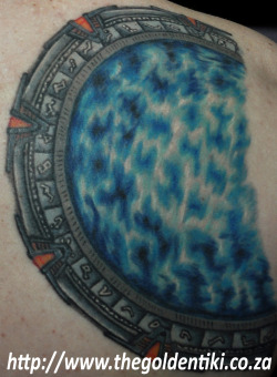 fuckyeahtattoos:  My SG-1 Stargate, part of a sci-fi backpiece that will feature ships from the shows that I adore. Each of the ships I will have represent the concept of creating one's own family, and exploring new places with them. The Stargate might not be a ship, but what better way to immortalise travelling to new worlds?  My artist, Ryan 'Busta' Bolton from The Golden Tiki in Johannesburg, South Africa, specialises in cartoons, and he completely amazed me with his attention to detail and intricate shading on this piece, so different from his normal style.
