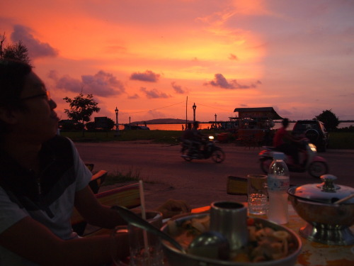 Enjoying some fantastic spicy Tom Yum soup and the technicolor sunset over the river in Koh Kong city, on the eve of another trial.