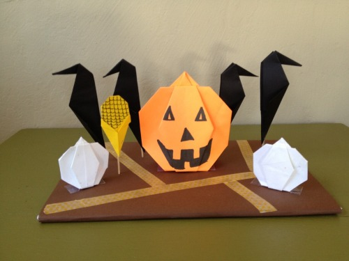 This is a Halloween Origami class project. I used washi tape for the *path* through the Pumpkin Patch. The crow is my design although I'm sure it's already been done since it is so simple. You cannot see it in this picture but I placed one of those small LED candles beneath the center pumpkin and I took it into the basement to see if it would work and it totally does!!! It looks so cool! They would look super awesome as home Halloween decor! Try it, you might like it! The pumpkin (and corn stalk) diagram I found on: http://en.origami-club.com I used color copy paper so the Origami model would stand up well. The platform is poster board that I covered with color copy paper. The crows are attached to toothpicks and stuck into the foam core board and then I clipped the ends off on the underside so it would lay flat.