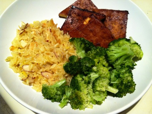 Tangerine Baked Tofu and Saffron-Garlic Rice  Original recipes from Veganomicon  I'd been neglecting my cookbooks for a while, but last weekend felt like the right time to make a list of all the recipes I want to make from the wonderful Veganomicon. My list is quite lengthy and I'm not even done yet! First up to make was their tangerine tofu and saffron-garlic rice. This is the most successful baked tofu I've made so far. Very flavorful with a nice texture. And the rice! It smells amazing and tastes even better. I served this with a simple side of steamed broccoli. Expect more recipes from the book in upcoming posts. Ingredients For the tofu: 1 pound extra-firm tofu 1 teaspoon tangerine zest 1/3 cup freshly squeezed tangerine juice (2 large or 3 small tangerines) 3 tablespoons lime juice 2 tablespoons soy sauce 1 tablespoon honey or agave nectar 1 tablespoon canola oil ½ teaspoon ground cumin 1/8 teaspoon allspice 2 tablespoons gold rum Freshly ground black pepper For the rice: 1 ½ cups water 1 vegetable bouillon cube Pinch of saffron threads 2 tablespoons olive oil 5 cloves garlic, pressed 1 small yellow onion, small dice 1 cup jasmine or basmati white rice Pinch of ground coriander Salt and freshly ground pepper 1/3 cup toasted, sliced almonds Directions For the tofu: 1. Press the tofu if not vacuum-packed. Cut block into eight squares. 2. Preheat the oven to 425 degrees. 3. Whisk together all of the marinade ingredients in a large, shallow baking pan. 4. Place the tofu squares into the marinade. 5. Bake for 45 minutes, flipping the tofu after 15 and 30 minutes. For the rice: 1. Boil water is a small saucepan. Add the bouillon cube and stir until dissolved. Turn off the heat, add saffron, and stir. Cover and remove from heat. 2. Heat oil in a medium pot. Sauté garlic for 30 seconds. Add onion and sauté until soft and translucent, about 5 minutes. Add the rice and sauté for 1 minute. Pour in the vegetable broth and add the coriander. Bring to a boil, cover, and lower heat to low. Simmer rice for 25 minutes. 3. Remove covered pot from heat and let rice stand for 10 minutes. 4. Fluff rice with fork, stir in almonds, and add salt and pepper to taste.  Servings: 4  Another recipe from the Veganomicon: Grilled Marinated Asian Tofu ♫ Music Pairing: Sky Ferreira – Everything is Embarrassing  From her upcoming Ghost EP. Video