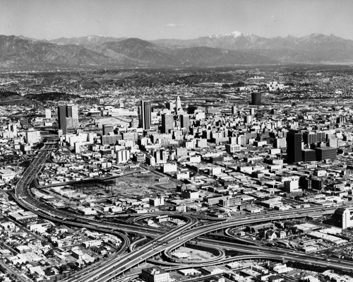 1970 aerial view of downtown Los Angeles, showing the interchange of the Santa Monica and Harbor Freeways, the future site of the Los Angeles Convention Center and Farmers Field, and a mid-redevelopment Bunker Hill. Part of the Dick Whittington Photograph Collection in the USC Digital Library.