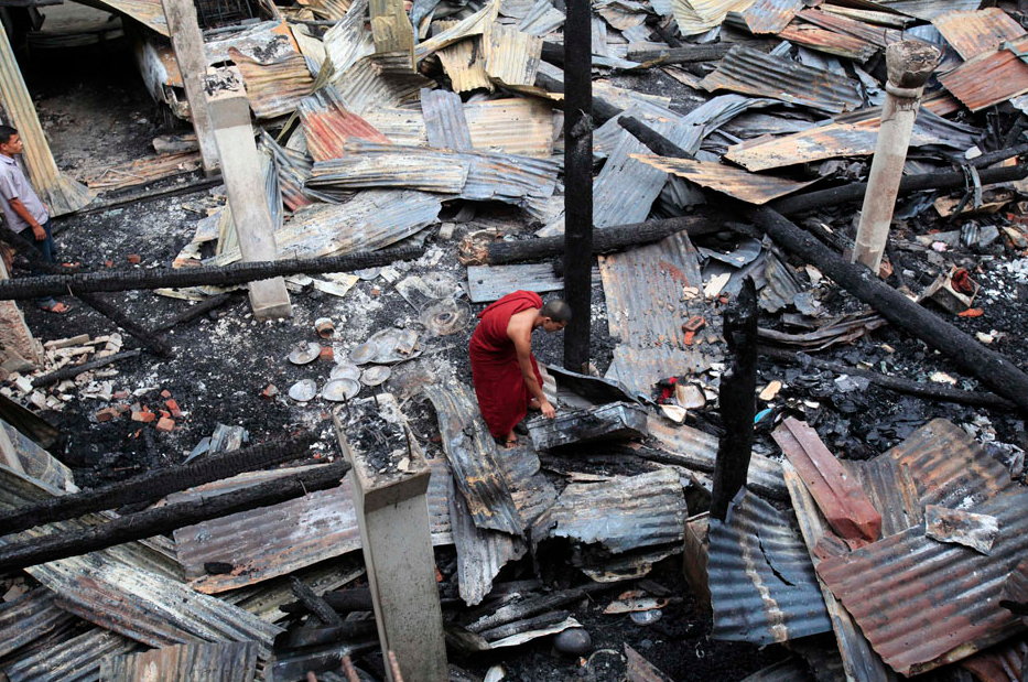 A Buddhist monk tries to salvage his belonging from a burnt temple after an attack by Muslims, in Cox's Bazar October 1, 2012.REUTERS/Andrew Biraj