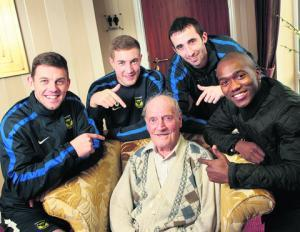 Oxford United players point at an old man