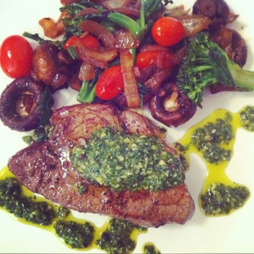 [HomeCookin] it's a debate steak night. Sautéed veggies + filet w/ chimichurri sauce.  Here's how:  [SAUTE] one large onion in olive oil until it starts to caramelize. Add a cup of small cremini mushrooms and saute on high heat. Season with salt + pepper. Throw in a punnet of cherry tomatoes and saute until they start to burst. Add some chopped green onions + roughly chopped bunch of broccolini and stir through for a couple of mins until greens have started to cook. Transfer to low oven to keep warm.   [BLEND] a bunch of cilantro, 3 cloves of garlic, some chives (or some green onion), juice of a lime, lime zest, salt/pepper and 3 tbsp olive oil. Blend in food processor/mixer until mixed. If you need a little more oil, add.   [SEAR] Filet Mignon, seasoned with salt and pepper in a hot pan for 6 mins on one side, then 4 mins on the other. Rest for 3 mins.   [SERVE] The steak, veggies and delicious Chimichurri sauce.   ENJOY!