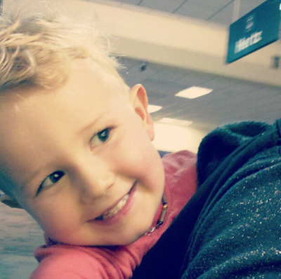 Kaspar, at the airport, on my back. All smiles.