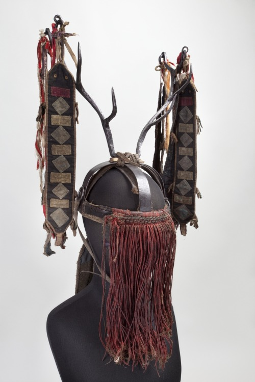 """Big"" Shaman's Headdress Nvikh The Peter the Great Museum of Anthropology and Ethnography ""This headdress of a ""big"" Evenk shaman (avun) made of steel was part of a full ritual costume worn by a shaman for very important rites and rituals. The structure of this headdress reflects its symbolic meaning and contains an archaic image of the model of the Universe. The hoop embodies the concept of the closed space of the world of people and solid earth. Two crossing arcs symbolize the parts of the world and the seasons. The cosmic vertical that reflects the sacral center of the Universe is embodied in the horns of the mythical deer that stands for the sun in the mythical beliefs of the peoples of northern Asia. The deer was one of the main characters in the myth about the celestial hunt and embodied the archaic concepts of the day and night and the cosmic order. The horns also symbolized the sacred deer – the helper spirit of the shaman, his draft animal that he rode to travel to other worlds. Long cloth ribbons embody snakes and lizards, the shaman's powerful helpers that accompany him in his ""travels"" to the lower world. They also symbolize the sacred birch – the totem tree of the shaman. It is also associated with the World Tree that symbolizes the Universe as a whole and Axis mundi – the cosmic axis connecting the spheres of the Universe. Such ritual headdresses were conditionally referred to as ""crowns""."""