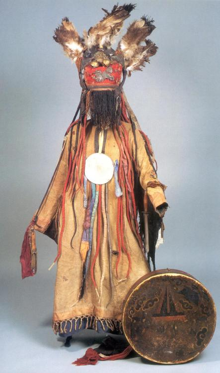 "Shaman's Costume Mongolia The National Museum of Mongolia ""This is an elaborate shaman's costume. The Caftan is of cotton with a woven geometrical pattern. The gown hanging over the chest has a nickel-plated brass mirror to ward off evil spirits. On the left arm is a dagger with a wooden handle with copper fittings as well as an iron blade. At the top of the shoulder blades, two tufts of owl feathers which, together with triangles of material hanging down from the underside of the sleeves, symbolize its ability to fly. The feathers of an eagle are also found at the top of his crown which consists of a cap of black wool and a red band across the front upon which a winged lion is mounted. It is made of chased copper and has, in addition to the wings, the claws of a bird. Skins of small animals, eagle feathers, and even bird claws highlight the connection between the shaman and the natural world. Above are round brass bells. The entire face is concealed by a black silk fringe. At the sides and the back of the cap are numerous snakes of material with coral eyes, as well as funnel-shaped iron rattles. The shaman's drum which matches this costume has a round frame of two layers of birch wood, a handle of leather, wound with silk and cloth, and above it a wire which is stretched across carrying seven coins of Chinese-Manchurian-origin rattles and bells. The outside of the drum-skin is painted with the flaming sor on a small altar, cloud-symbols, garuda, dragon, tiger and lion, all indications of how strongly the so-called ""yellow shamanism"" was overlaid with Buddhist elements. The wooden drumstick has a fur-covered head and a metal stick with eight rattle–rings."""
