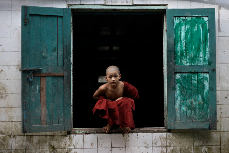An ethnic Shan Buddhist Novice Monk sits on a window sill after attending classes at Thone Htat Monastery in Yangon October 3, 2012. Thone Htat monastery houses a free school run by Buddhist monks and attended by 37 Buddhist novice monks and 10 other students. All of the Buddhist attendees are from the Shan, Pa-O and Wa ethnic groups. REUTERS/Soe Zeya Tun