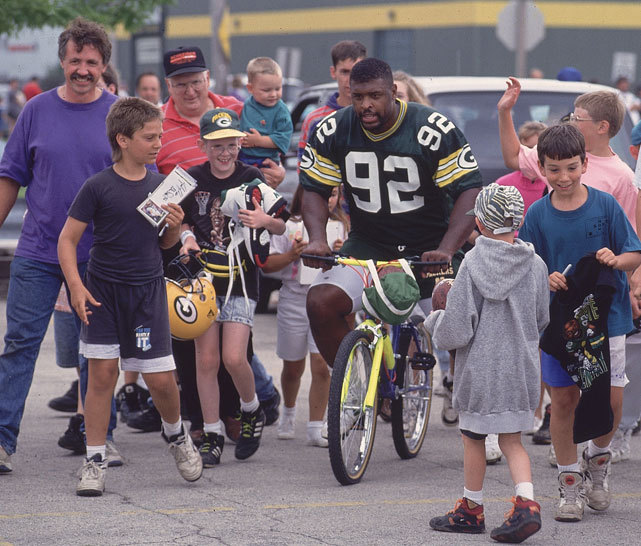 Reggie White is a hit among Packers fans as he goes for a bike ride during Green Bay's training camp in 1993. (John Biever/SI) GALLERY: Athletes Riding Bicycles