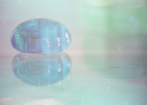 This is a small, round piece of blue glass sitting on a glass table (reflection!) layered with a free texture I found on flickr.